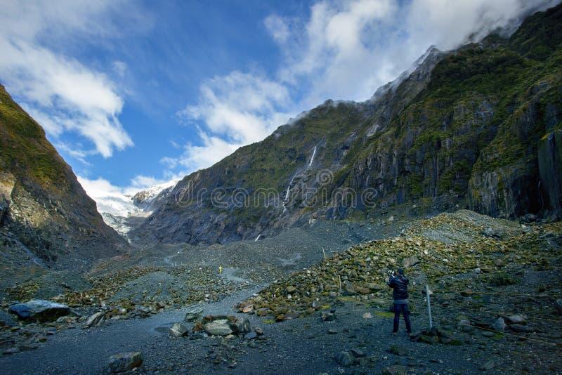 Fotógrafo que toma uma fotografia na geleira uma de Franz josef da maioria de destino de viagem natural popular em southland Nova fotografia de stock