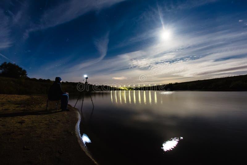 Fotógrafo que toma una foto del paisaje épico de la noche imagen de archivo libre de regalías