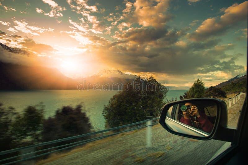 Fotógrafo que toma una fotografía del cielo determinado del sol mientras que viaja fotos de archivo libres de regalías