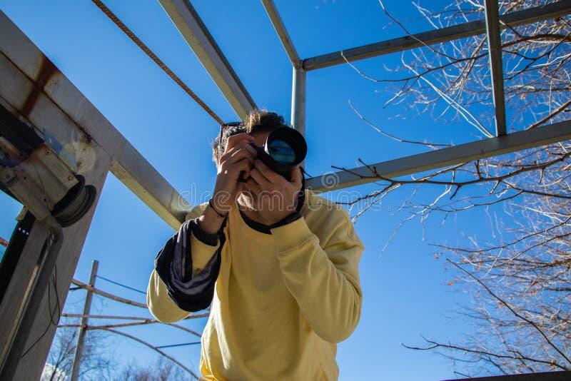 Fotógrafo que toma una imagen que lleva una camisa amarilla imagen de archivo