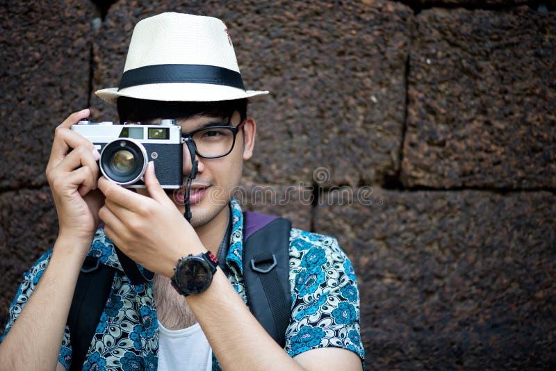 Fot?grafo Traveler del hombre joven con la mochila que toma la foto con su c?mara, Gran Muralla en fondo en el lugar hist?rico fotos de archivo