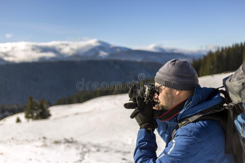 Fotógrafo turístico de Hiker em roupas quentes com mochila e câmera fotografando o vale de neve e picos de montanha lenhosos imagem de stock royalty free