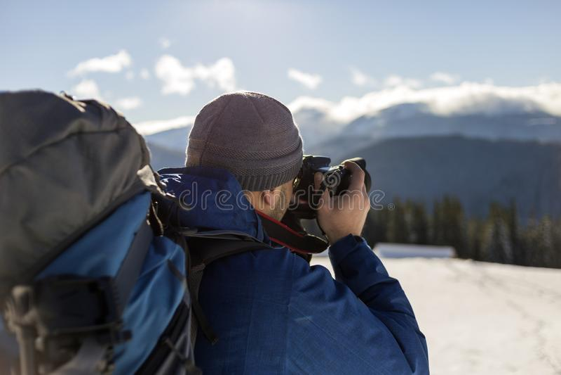 Fotógrafo turístico de Hiker em roupas quentes com mochila e câmera fotografando o vale de neve e picos de montanha lenhosos imagem de stock
