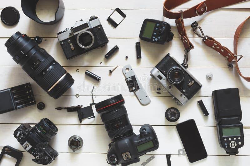 Fotógrafo Workplace, câmera, lentes e acessórios no fundo de madeira branco Vista superior foto de stock