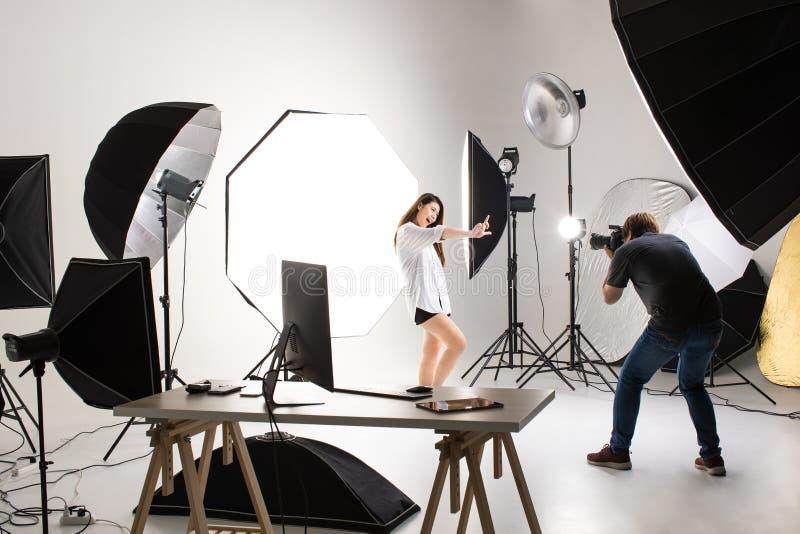 Fotógrafo y modelo bonito que trabajan en estudio moderno de la iluminación imagen de archivo