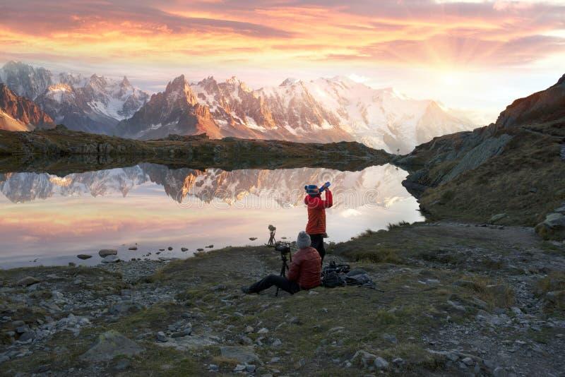 Fotógrafos de los escaladores en la puesta del sol foto de archivo