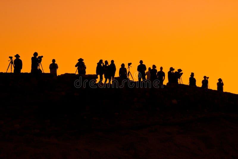 Fotógrafos debajo del cielo anaranjado de la puesta del sol imagenes de archivo