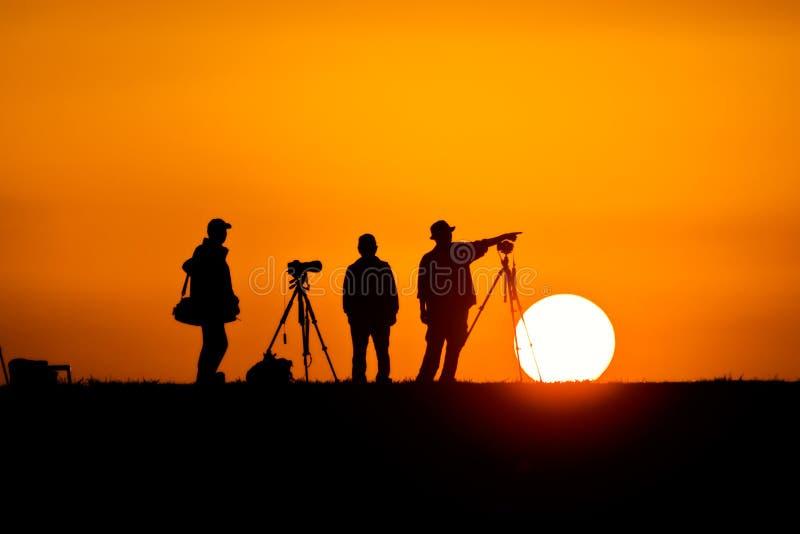 Fotógrafos silueteados contra el sol de configuración imágenes de archivo libres de regalías