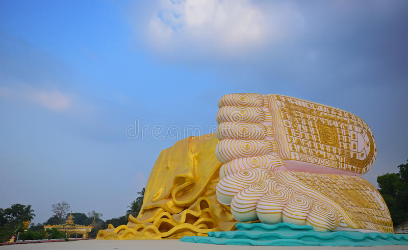 Fot av Buddha med den gula ämbetsdräkten som täcker benen mot bakgrund för blå himmel arkivbild