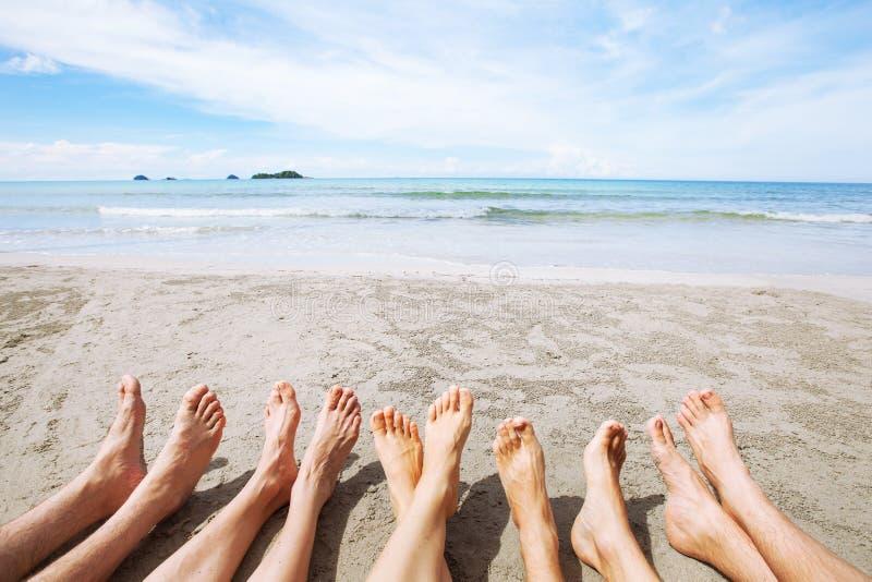 Fot av familjen eller gruppen av vänner på stranden, många personer som tillsammans sitter royaltyfri fotografi