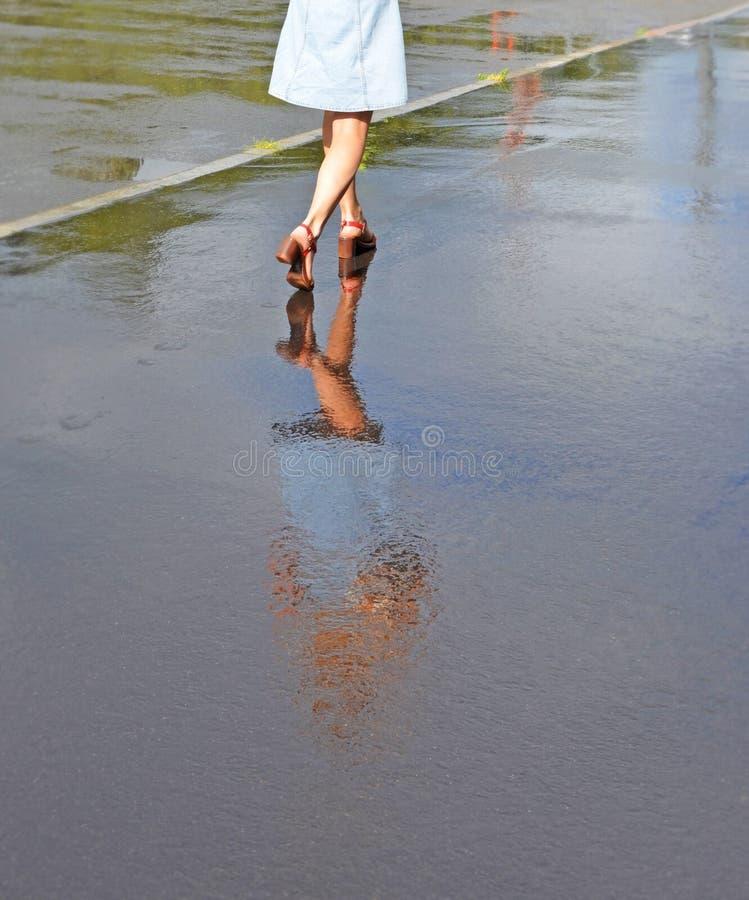 Fot av flickan och hennes reflexion i vatten på trottoaren royaltyfri bild