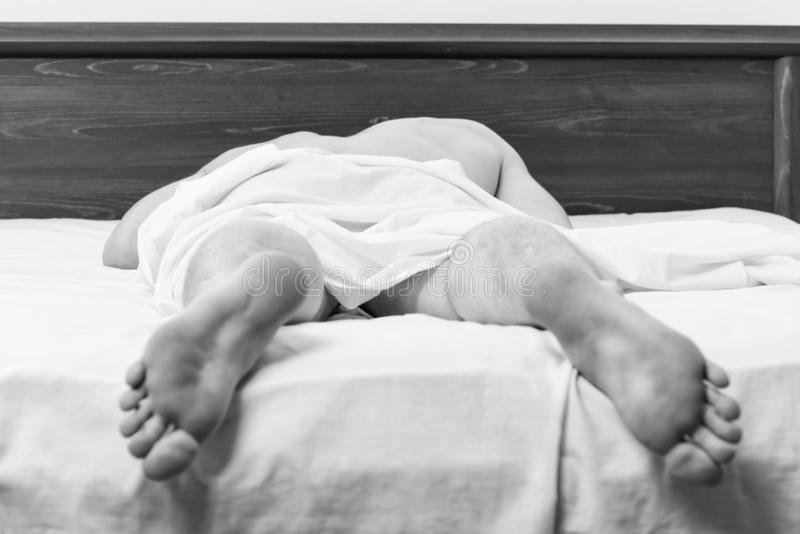 Fot av mannen som sover i bekv?m s?ng En ung man som vaknar upp i s?ng och str?cker hans armar Man p? underlag royaltyfria bilder