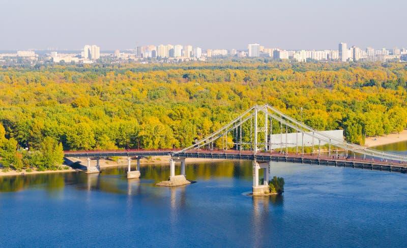 Fot- bro över en Dnieper för molnig himmel flod i Kiev royaltyfria bilder