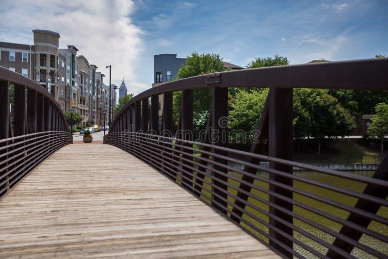 Fot- bro över ett damm i en parkera i den västra midtownen Atlanta fotografering för bildbyråer