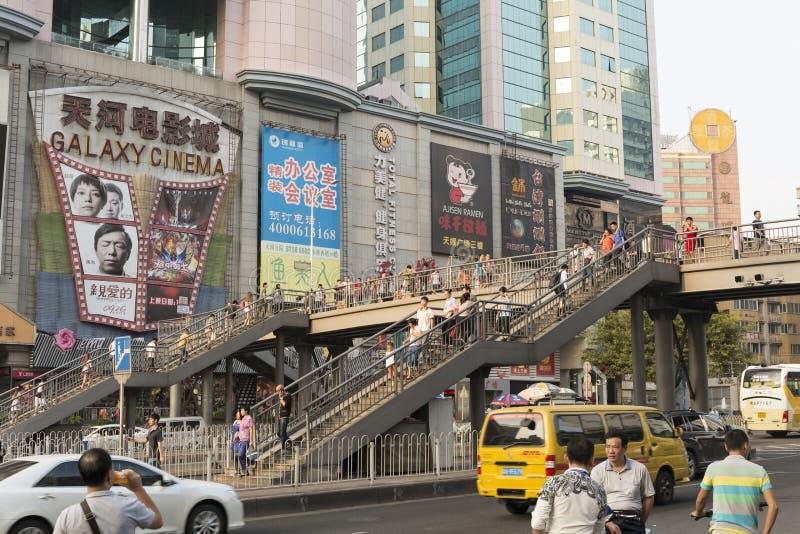 Fot- bro; upptagen väg med planskild korsningspången; upptagen gata i centrum av Guangzhou Kina med overbridge; flygparadbro arkivfoto