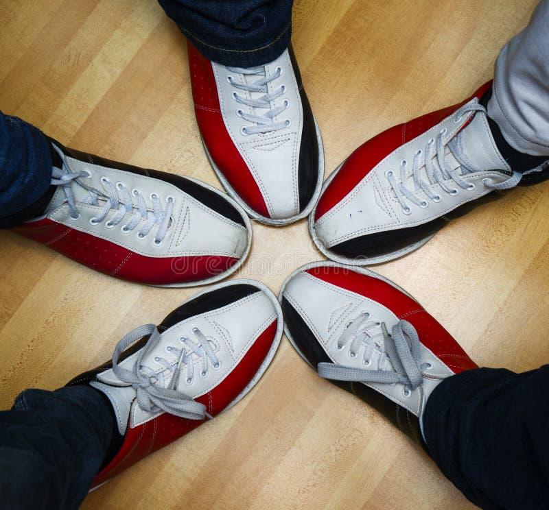 Fot för barn` s i skor och en bowlingklot royaltyfri bild