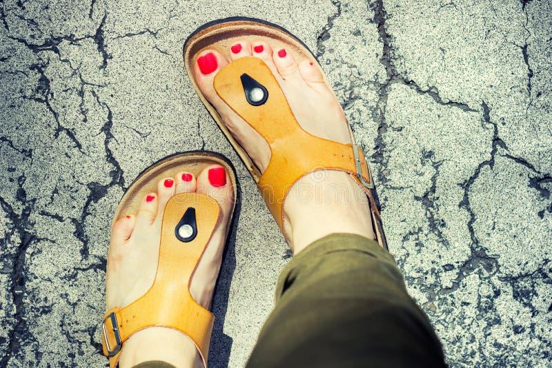 Fot för kvinna` s i gula stilfulla sommarsandaler arkivfoto