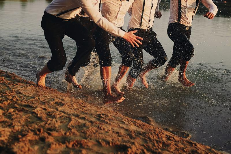 Fot f?r man` s i vattnet De har gyckel, spelar och plaskar vatten runt om dem Sommar royaltyfria bilder