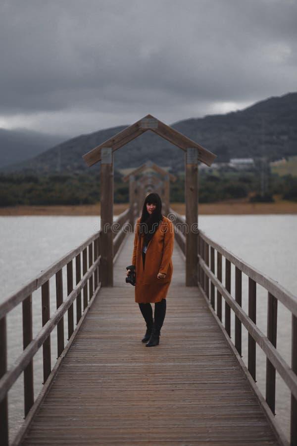 Fot?grafo moreno de la mujer con la trenca anaranjada en un puente foto de archivo