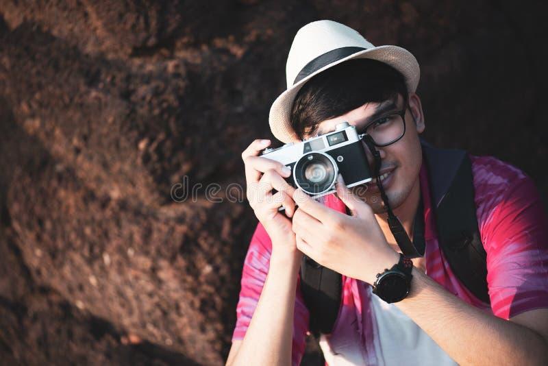 Fot?grafo Traveler del hombre joven con la mochila que toma la foto con su c?mara, Gran Muralla en fondo en el lugar hist?rico imágenes de archivo libres de regalías