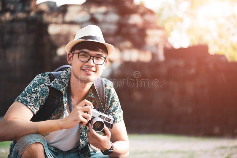 Fot?grafo Traveler del hombre joven con la mochila que toma la foto con su c?mara, Gran Muralla en fondo en el lugar hist?rico foto de archivo libre de regalías