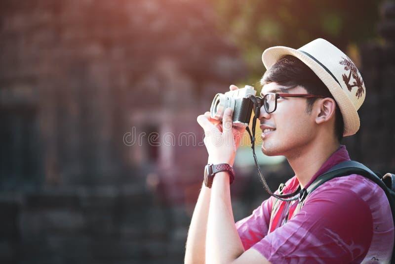 Fot?grafo Traveler del hombre joven con la mochila que toma la foto con su c?mara, Gran Muralla en fondo en el lugar hist?rico fotos de archivo libres de regalías