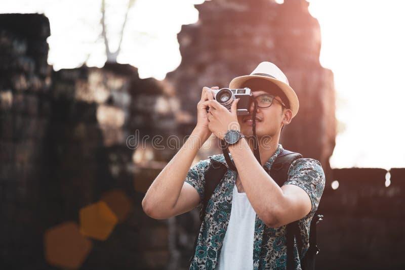 Fot?grafo Traveler del hombre joven con la mochila que toma la foto con su c?mara retra de la pel?cula, Gran Muralla en fondo en  fotografía de archivo libre de regalías
