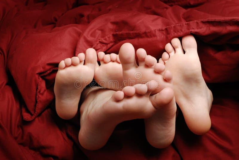 Fot i säng med rött vila för filt fotografering för bildbyråer