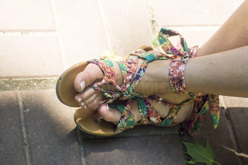 Fot i sandaler på fonetegelplattor arkivfoto