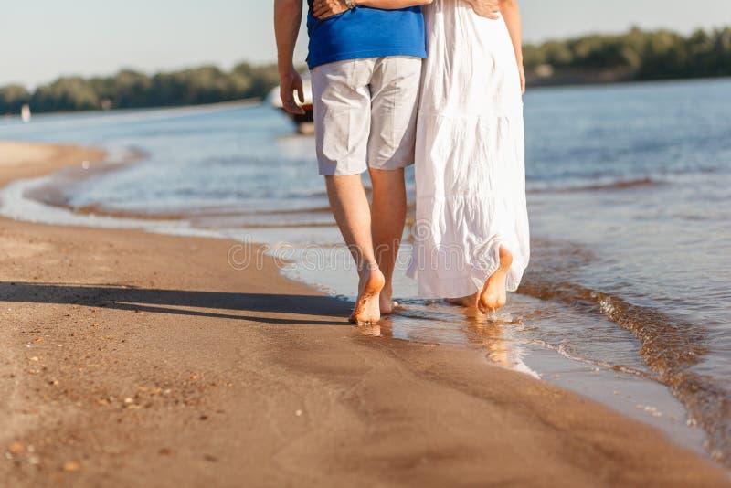 Fot i vattensommaren Unga barfota par som promenerar stranden k?rlekshistoria f?r tr?dg?rds- flicka f?r pojke kyssande Vinkar och royaltyfri bild