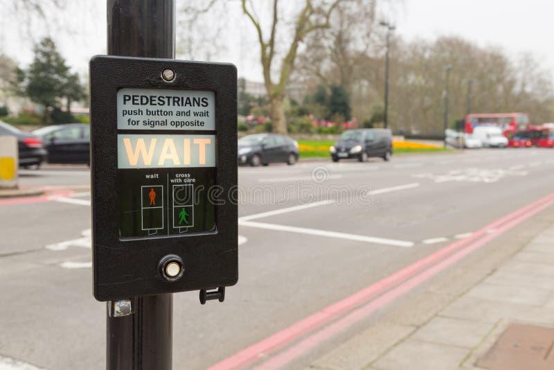 Fot- knapp som indikerar väntan i London, UK royaltyfri bild
