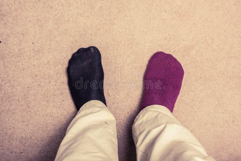 Fot med udda sockor på matta arkivfoto