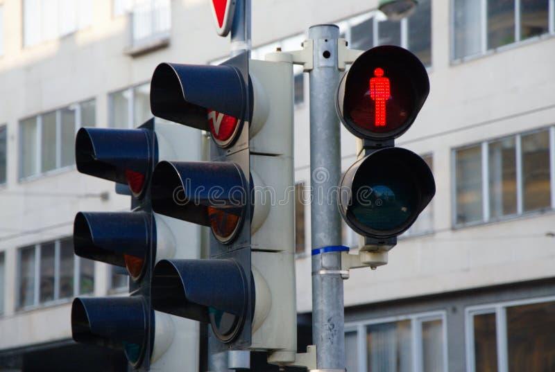 Fot- röd trafikljusvisning och stad i bakgrunden royaltyfria foton