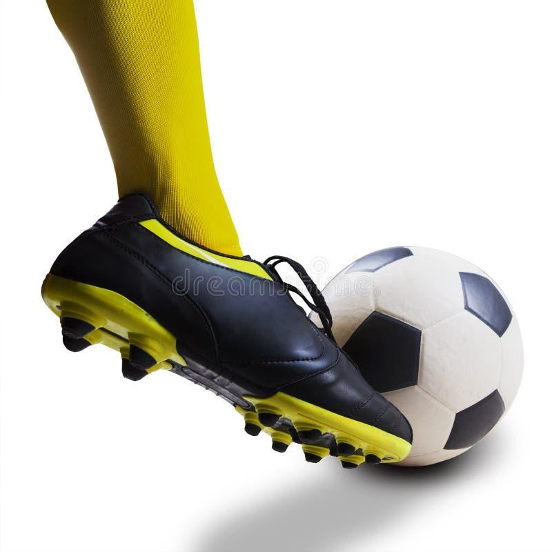Fot som sparkar den isolerade fotbollbollen royaltyfria bilder
