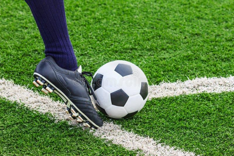 Fot som sparkar fotbollbollen royaltyfri fotografi