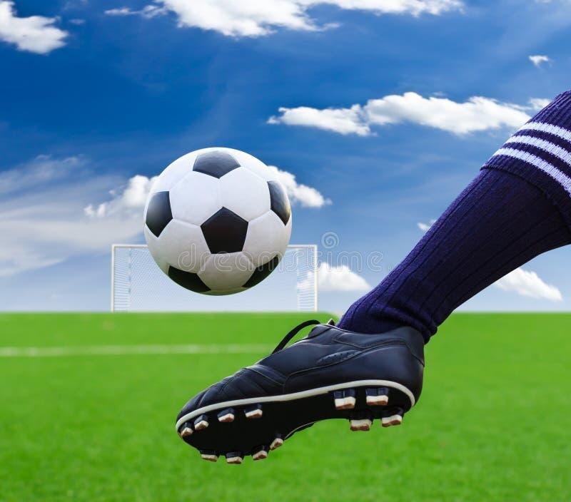 Fot som sparkar fotbollbollen arkivfoto