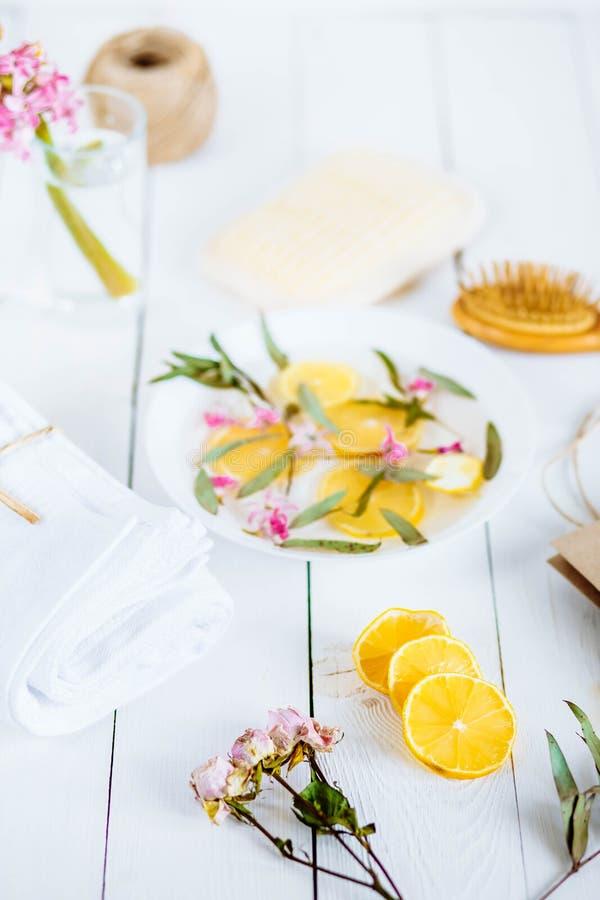Fotbad i bunke med limefrukt och tropiska blommor, brunnsortpedikyrbehandling, bästa sikt arkivbilder