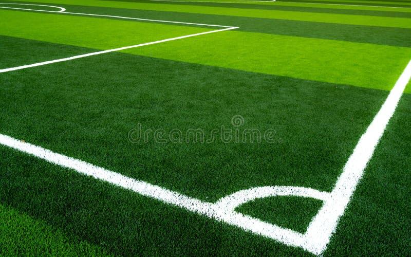 fotboll för fältgräsgreen Töm det konstgjorda torvafotbollfältet med den vita linjen Sikt från hörnet av fotbollfältet sport royaltyfri fotografi
