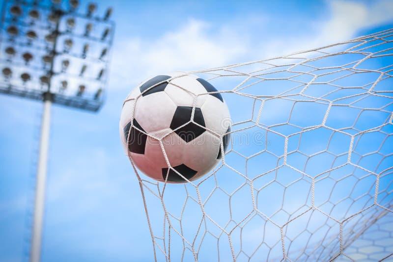 Fotboll i mål förtjänar royaltyfri bild