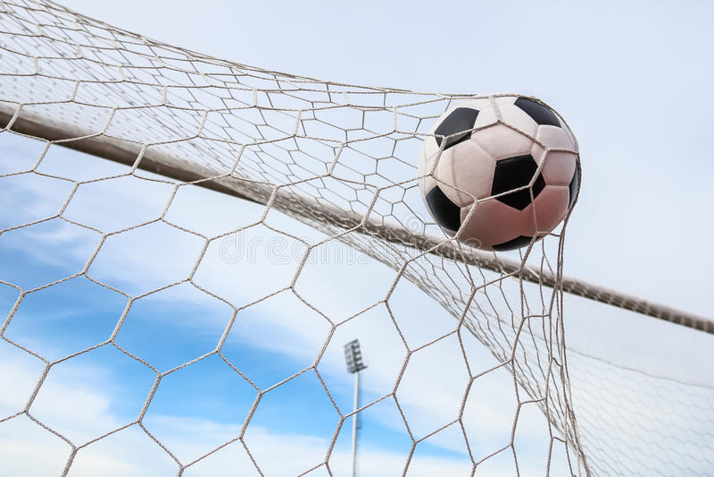 Fotboll i målet förtjänar royaltyfri bild