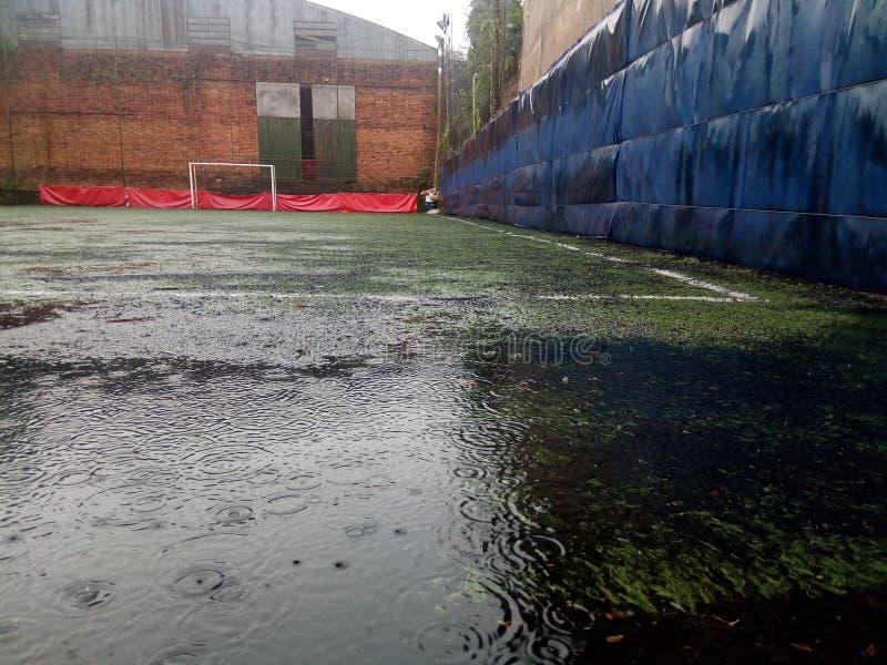 Fotboll i regnet royaltyfri foto