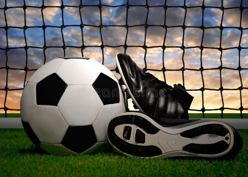 Fotboll klumpa ihop sig och skor fotografering för bildbyråer