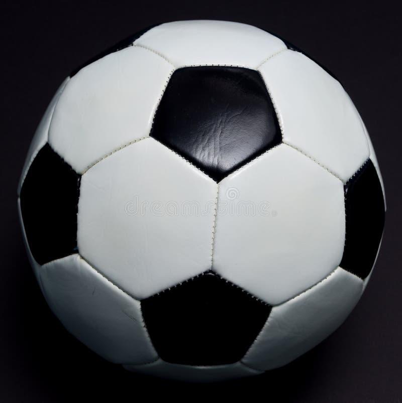 Fotboll klumpa ihop sig på svart arkivbilder