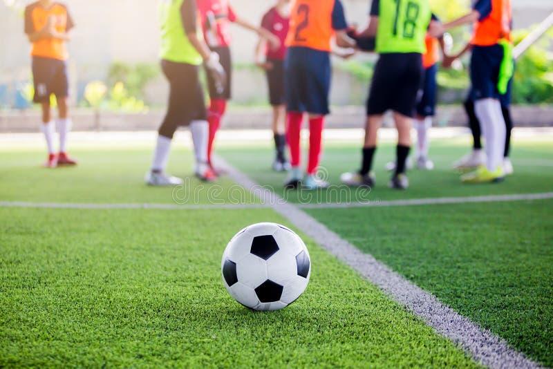 Fotboll på grön konstgjord torva med oskarpt anseende för fotbollspelare fotografering för bildbyråer