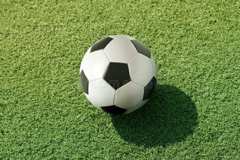 Fotboll på grönt gräs royaltyfria foton