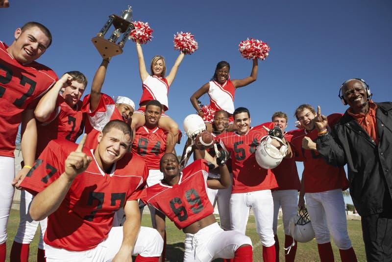 Fotboll Team With Cheerleaders And Coach som firar framgång på fält royaltyfri bild