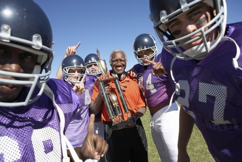 Fotboll Team And Coach With Trophy som firar Victory On Field royaltyfri bild