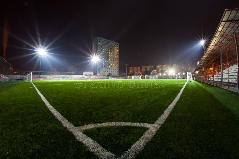 Fotbollarena i upplysta ljusa strålkastare för natt arkivfoto