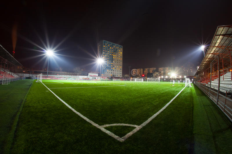 Fotbollarena i upplysta ljusa strålkastare för natt royaltyfri fotografi
