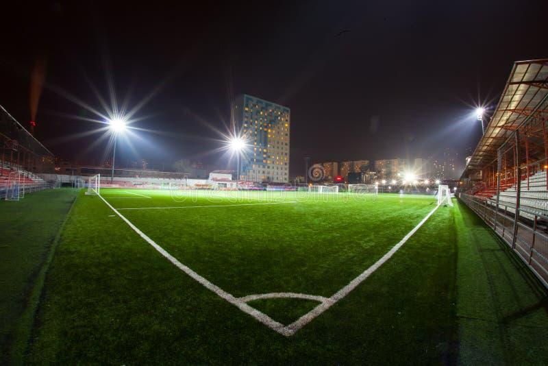 Fotbollarena i upplysta ljusa strålkastare för natt fotografering för bildbyråer